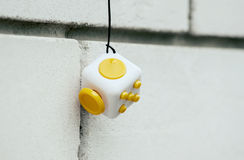 Yellow white cube antistress on brick wall background, Fidget Cu Stock Photo