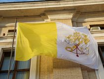 Yellow and white flag of the Vatican state with the symbol of th. Waving yellow and white flag of the Vatican papal state with the symbol of the two crossed keys stock images