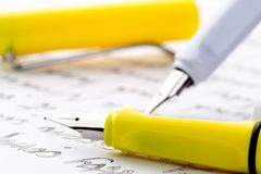 Yellow and white fountain pens on a letter royalty free stock photography