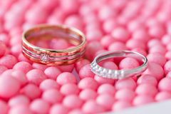 Yellow and white gold wedding ring with diamond. pink balls and bubbles background. Original tray for the ceremony of. Marriage Royalty Free Stock Photos