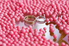 Yellow and white gold wedding ring with diamond. pink balls and bubbles background. Original tray for the ceremony of. Marriage Stock Photo