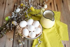 Easter eggs on willow branches with white eggs in yellow plate on the wooden table stock image