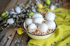 Easter eggs on willow branches with white eggs in yellow plate on the wooden table stock images