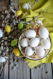 Easter eggs on willow branches with white eggs in yellow plate on the wooden table royalty free stock photography