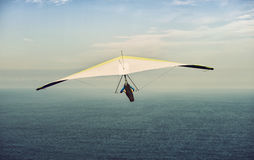 Yellow and white hang glider in flight off with clouds sky Stock Images