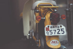 Yellow and White Motor Scooter With 5725 License Plate Stock Image