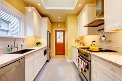 Yellow and white narrow modern kitchen. Stock Image