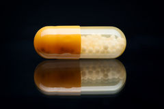 Yellow and White pill (capsule) macro shot, isolated on black Stock Photos