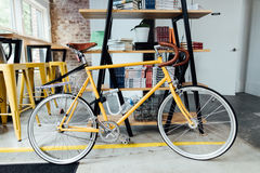 Yellow and White Road Bike Near Beige and Black Wooden Shelf Royalty Free Stock Images