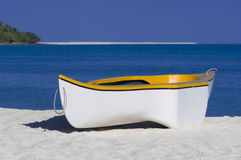Yellow and white rowing boat. On a coral sand beach in the Maldives stock photography