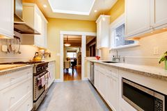 Yellow and white simple kitchen with skylight. Stock Photography