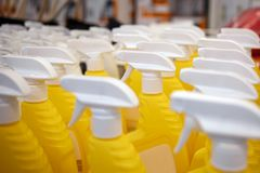 Yellow bottles in the store. Sprayers for water. Beautiful sprayers are on the supermarket shelves stock images