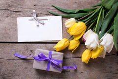 Yellow and white spring tulips, empty tag  and wrapped  box Royalty Free Stock Photography