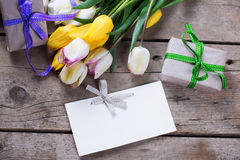 Yellow and white spring tulips, wrapped  boxes with presents  an Stock Image