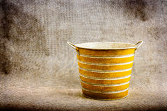 A yellow and white striped metal bucket against a brown, textured background Stock Photo