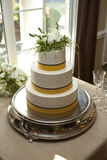 Yellow and white three tiered cake Royalty Free Stock Images