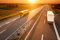 Yellow and white truck in motion blur on the highway. At sunset Royalty Free Stock Photography