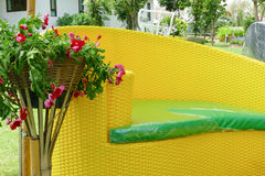 Yellow wicker style couch with green leather in the garden Stock Photography
