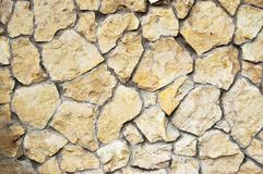Yellow wild stone wall background Stock Images