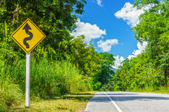 Yellow winding road sign at roadside Stock Photos