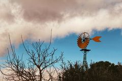 Yellow windmill with tale vane under cloudy and windy weather. In the countryside stock photos