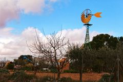 Yellow windmill with tale vane under cloudy and windy weather. In the countryside stock images