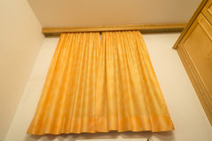 Yellow window curtain. Yellow home curtain with window over the room wall Stock Image