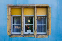 Yellow window frame and blue wall. Blue and yellow window frame in the small city of Colmar in the Alsace region in France Stock Photo