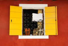 Yellow window, red wall, shoes  on the windowsill Royalty Free Stock Images