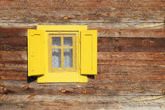 Yellow window on wooden wall Stock Photography