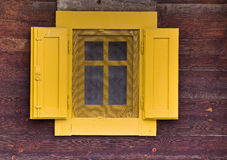 Yellow window on wooden wall Stock Photos