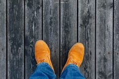 Yellow winter boots on wooden planks background. Top view Stock Photo