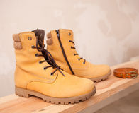 Yellow Winter shoes on wooden background Royalty Free Stock Photos