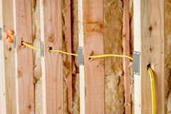 Yellow wire fed through wood studs in new home construction with steel protector plates. Metal plates protect electrical wire in wood studs of a home under royalty free stock photo