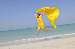 Yellow woman running on beach Royalty Free Stock Photography