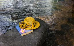 Yellow women hat and book on the rock in waterfall Royalty Free Stock Images