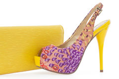 Yellow women stiletto shoe with matching bag. On white background royalty free stock image