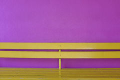 Yellow wood bench on violet wall background Stock Image