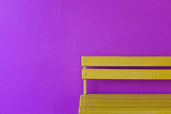Yellow wood bench on vivid violet wall background Royalty Free Stock Photos