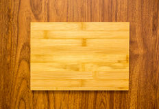 Yellow wood plate on brown texture wood background Royalty Free Stock Photo