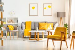 Yellow wooden armchair in bright living room interior with grey royalty free stock image