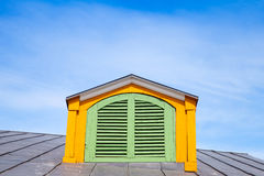 Yellow wooden attic window with green shutters Royalty Free Stock Image
