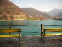 Yellow wooden bench along the turquoise blue lake in Slovenia, Europe.At the background of the Alps and the hills. Unspoiled natur. E, greenery and clean water stock photo