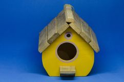 Yellow wooden bird house. Against blue background royalty free stock photography