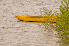 Yellow wooden boat adrift in lake. Small wooden yellow boat drifting in lake with choppy water with a lush green bush covering the rear part of the boat Stock Photo