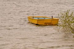 Yellow wooden boat adrift in lake. Small wooden yellow boat drifting in lake with choppy water with a lush green bush extending from the shore over the water Royalty Free Stock Photography