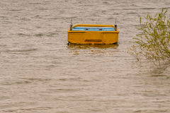 Yellow wooden boat adrift in lake. Small yellow wooden boat drifting in lake with choppy water with a lush green bush extending from the shore over the water Royalty Free Stock Images