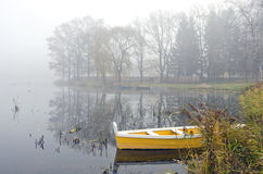 Yellow wooden boat on autumn lake and morning mist Royalty Free Stock Images
