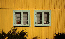 Yellow wooden building with windows. Exterior of a bright yellow wooden building with two double windows Royalty Free Stock Image
