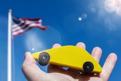 Yellow wooden car holding against blue sky with american flag and sun flare royalty free stock image